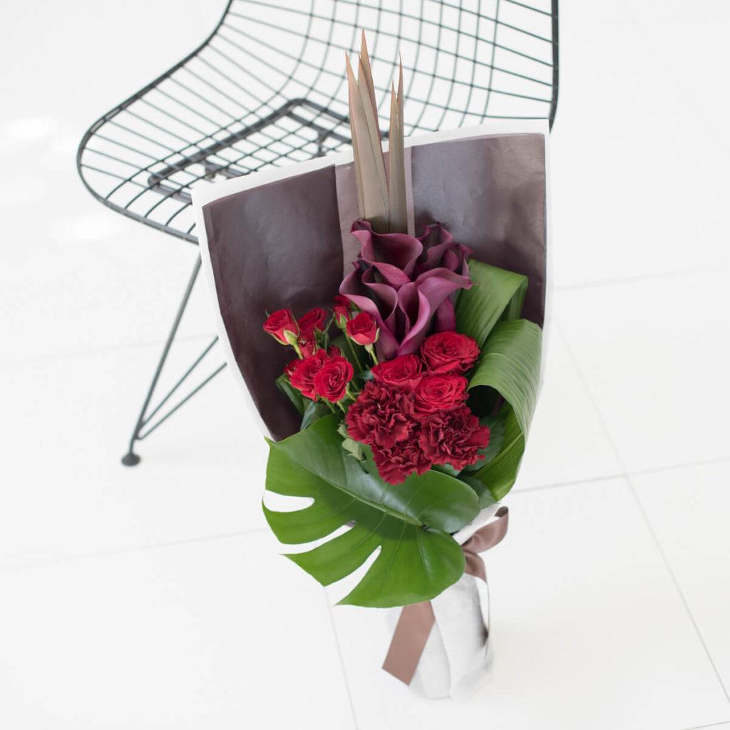 花キューピットのサブブランド、プシュケのフラワーブーケ。テーマはモダン。赤バラとワイン色のカラーの花束。