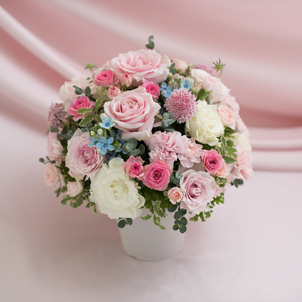 花キューピットのサブブランド、プシュケの生花アレンジメント。テーマはキュート。ピンク白水色とグレイッシュなグリーンのアレンジメント。