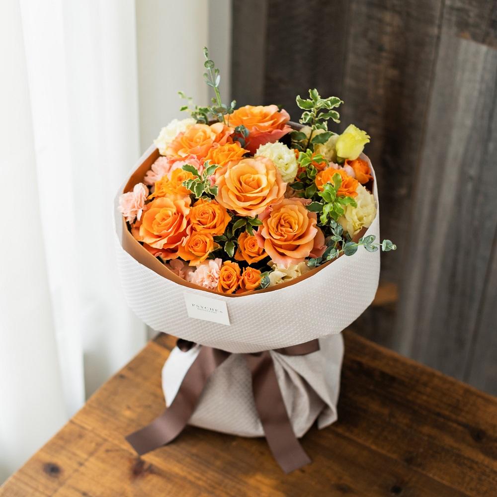 花キューピットのサブブランド、プシュケの生花ブーケ。テーマはウォーム。オレンジ色の花束。