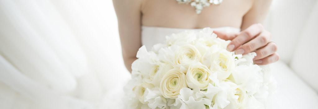 ウェディングドレス姿の花嫁と白いブーケの画像。